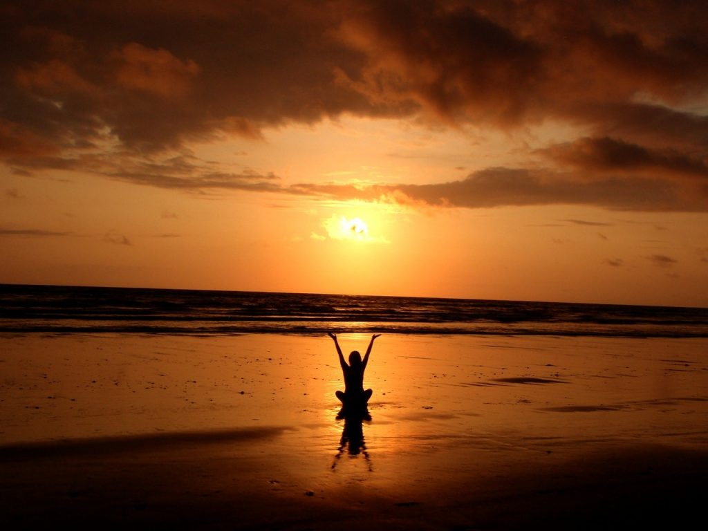 person doing yoga in front of sun silhoutte