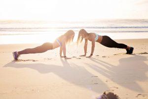 two women doing yoga on beach sunset